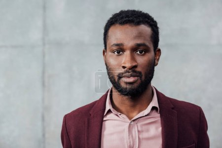 Photo for Selective focus of african american casual businessman looking at camera on grey background - Royalty Free Image