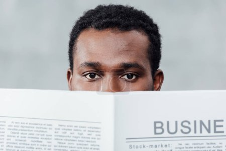 african american casual businessman holding newspaper in front of face and looking at camera