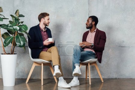 multiethnic men in casual clothes sitting, drinking coffee and talking in waiting hall