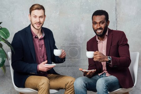 handsome multiethnic men sitting, looking at camera and drinking coffee in waiting hall