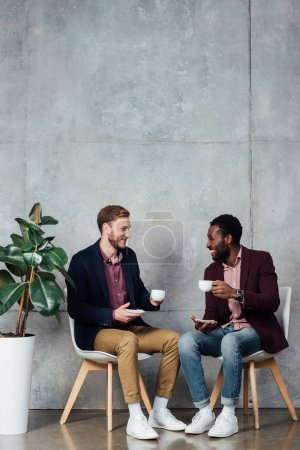 smiling men sitting and drinking coffee while talking in waiting hall