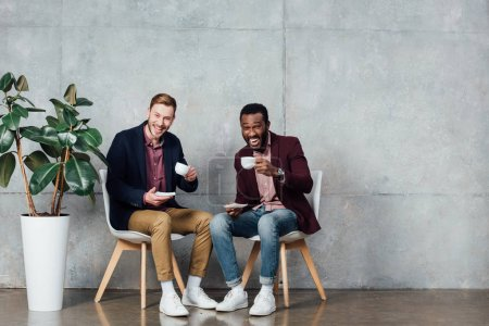 multiethnic men sitting, looking at camera and drinking coffee in waiting hall