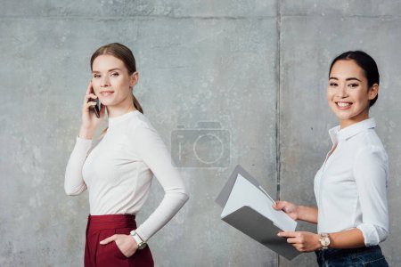 multiethnic casual businesswomen talking on smartphone and holding folder with documents in office