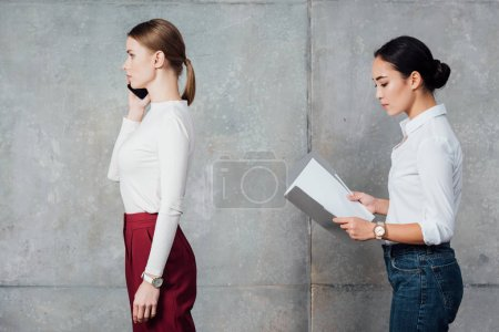serious multiethnic casual businesswomen talking on smartphone and holding folder with documents in office
