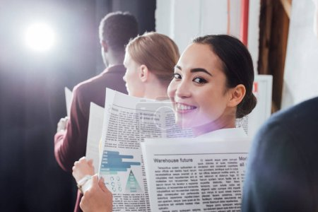 attractive asian businesswoman looking at camera and holding newspaper with colleagues on background