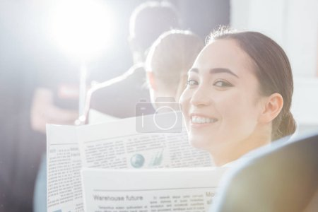 selective focus of asian businesswoman looking at camera and holding newspaper with colleagues on background