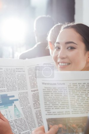 beautiful asian businesswoman looking at camera and holding newspaper with colleagues on background