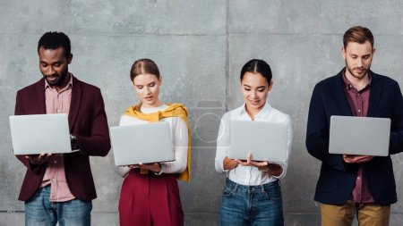 Photo for Focused multiethnic casual businesspeople using laptops in waiting hall - Royalty Free Image
