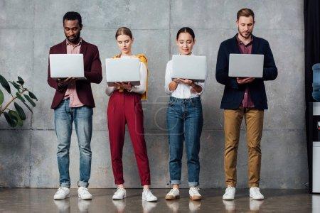 Photo pour Hommes d'affaires occasionnels multiethniques concentrés utilisant des ordinateurs portables dans la salle d'attente - image libre de droit