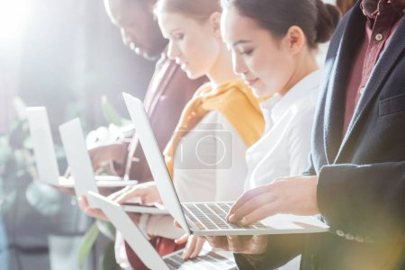 selective focus of businesspeople using laptops with backlit on background