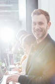 selective focus of handsome smiling businessman looking at camera with colleagues using laptops on background