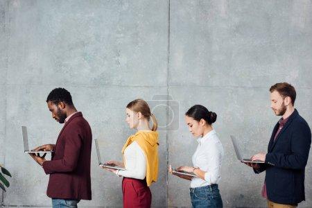 Foto de Empresarios informales multiétnicos usando computadoras portátiles en la sala de espera - Imagen libre de derechos