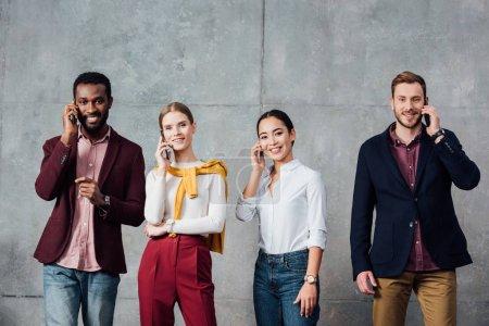 Foto de Sonrientes empresarios casuales multiétnicos hablando en teléfonos inteligentes en la sala de espera - Imagen libre de derechos
