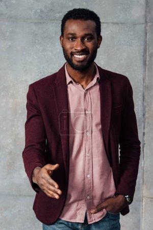 Photo pour Souriant afro-américain occasionnel homme d'affaires étirant la main pour poignée de main sur fond gris - image libre de droit