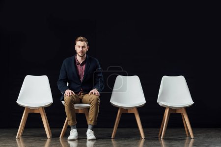 serious man sitting on chair and looking at camera isolated on black