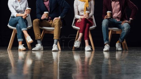 cropped view of people in casual clothes sitting on chairs with coffee to go