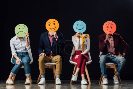 group of people sitting on chairs and holding face cards with various emotions isolated on black