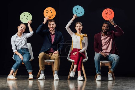 Photo for Multiethnic people sitting on chairs and holding face cards with various emotions isolated on black - Royalty Free Image