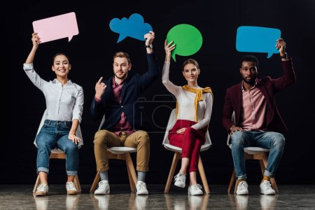 multiethnic people sitting and holding speech bubbles and thought bubble isolated on black