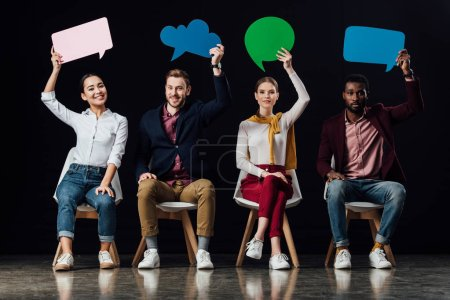 smiling multiethnic people holding speech bubbles and thought bubble isolated on black
