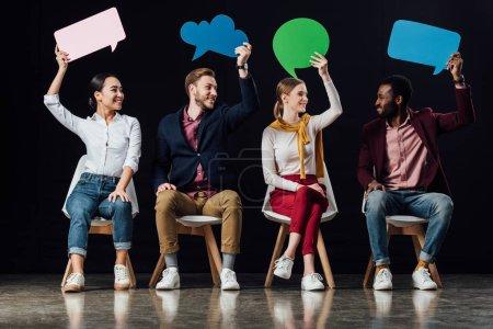 Photo pour Heureux peuple multiethnique tenant des bulles et des bulles de pensée isolée sur fond noir - image libre de droit