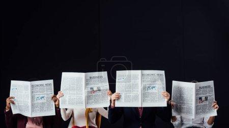 groupe d'hommes d'affaires occasionnels aux visages obscurs lisant des journaux d'affaires isolés sur noir