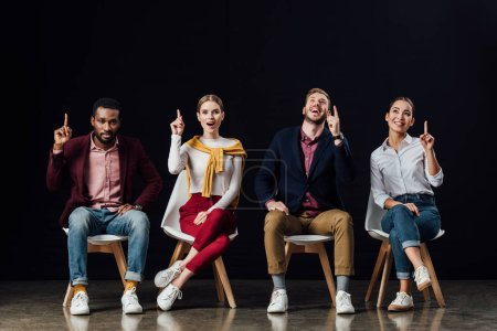 Photo for Multiethnic group of people sitting on chairs and showing idea gestures isolated on black - Royalty Free Image