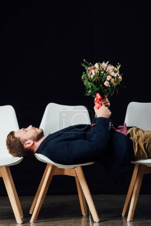 man with eyes closed lying on chairs and holding flowers isolated on black