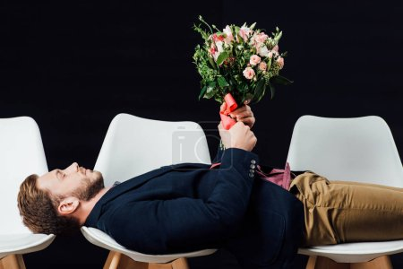 Photo for Handsome man in casual clothes lying on chairs and holding flowers isolated on black - Royalty Free Image