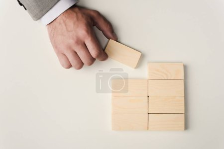 Photo for Cropped view of man holding brick in hand near wooden blocks symbolizing building success isolated on white - Royalty Free Image