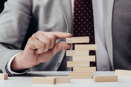 cropped view of man with wooden blocks symbolizing building success