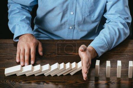 Foto de Vista parcial del hombre sentado en el escritorio e impidiendo la caída de bloques de madera - Imagen libre de derechos
