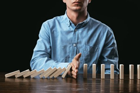 cropped view of man sitting at desk and preventing wooden blocks from falling