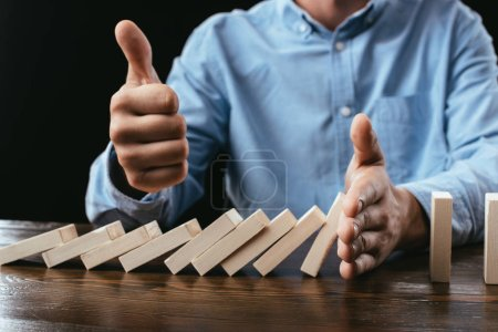 Photo for Partial view of man sitting at desk, showing thumb up sign and preventing wooden blocks from falling - Royalty Free Image