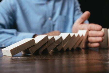 Foto de Recortada la visión del hombre en el escritorio impidiendo la caída con la mano de bloques de madera - Imagen libre de derechos