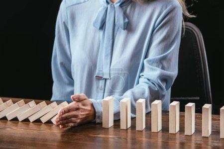 Foto de Vista recortada de la mujer sentada a la mesa y evitando que los bloques de madera caigan con la mano aislada en negro - Imagen libre de derechos