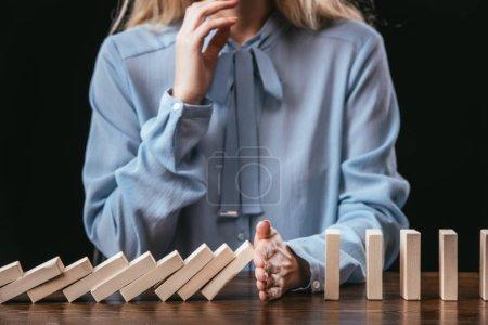 Photo pour Vue recadrée de la femme en chemisier bleu assis au bureau et empêchant les blocs de bois de tomber à la main - image libre de droit