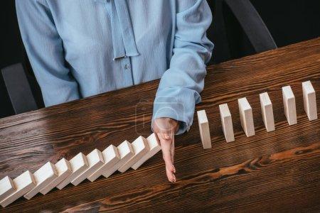 Photo pour Vue partielle de la femme en blouse bleue assise au bureau et empêchant les blocs de bois de tomber à la main - image libre de droit
