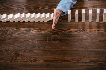 Photo pour Vue recadrée de la femme assise au bureau et empêchant les blocs de bois de tomber avec de l'espace de copie - image libre de droit