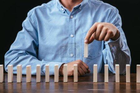 Photo pour Vue recadrée de l'homme ramassant la brique de bois sur la table isolée sur noir - image libre de droit