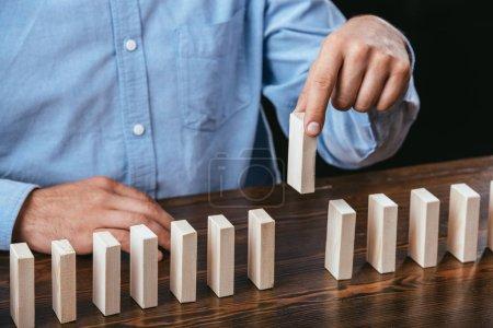 Photo pour Recadrée de l'homme cueillait des briques en bois hors ligne sur table - image libre de droit