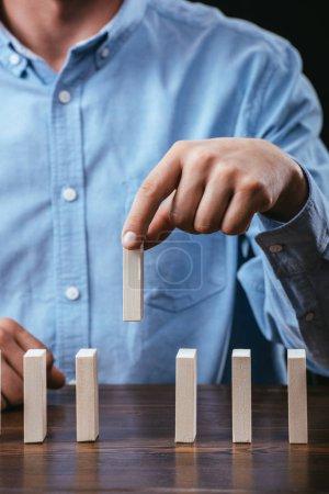Photo pour Vue recadrée de l'homme ramassant la brique de bois sur la table - image libre de droit