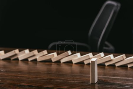 Photo for Selective focus of wooden block with fallen bricks row on background isolated on black - Royalty Free Image