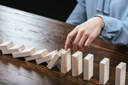 cropped view of woman sitting at table and preventing wooden blocks from falling
