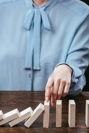 cropped view of woman in blue blouse sitting at desk and preventing wooden blocks from falling