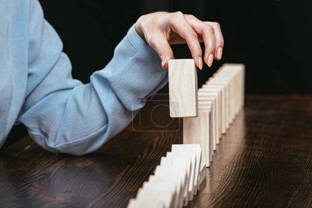Photo pour Vue partielle de femme cueillette en bois brique de rangée de blocs isolés sur fond noir - image libre de droit