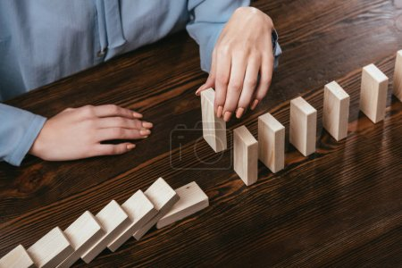 partial view of woman picking wooden brick from row of blocks on desk
