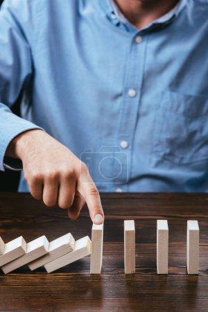 Photo pour Recadrée de l'homme, empêchant des blocs de bois de tomber avec le doigt - image libre de droit