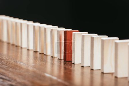 row of wooden blocks with red one on desk isolated on black