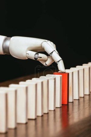 robotic hand picking red wooden brick from row of blocks on desk isolated on black